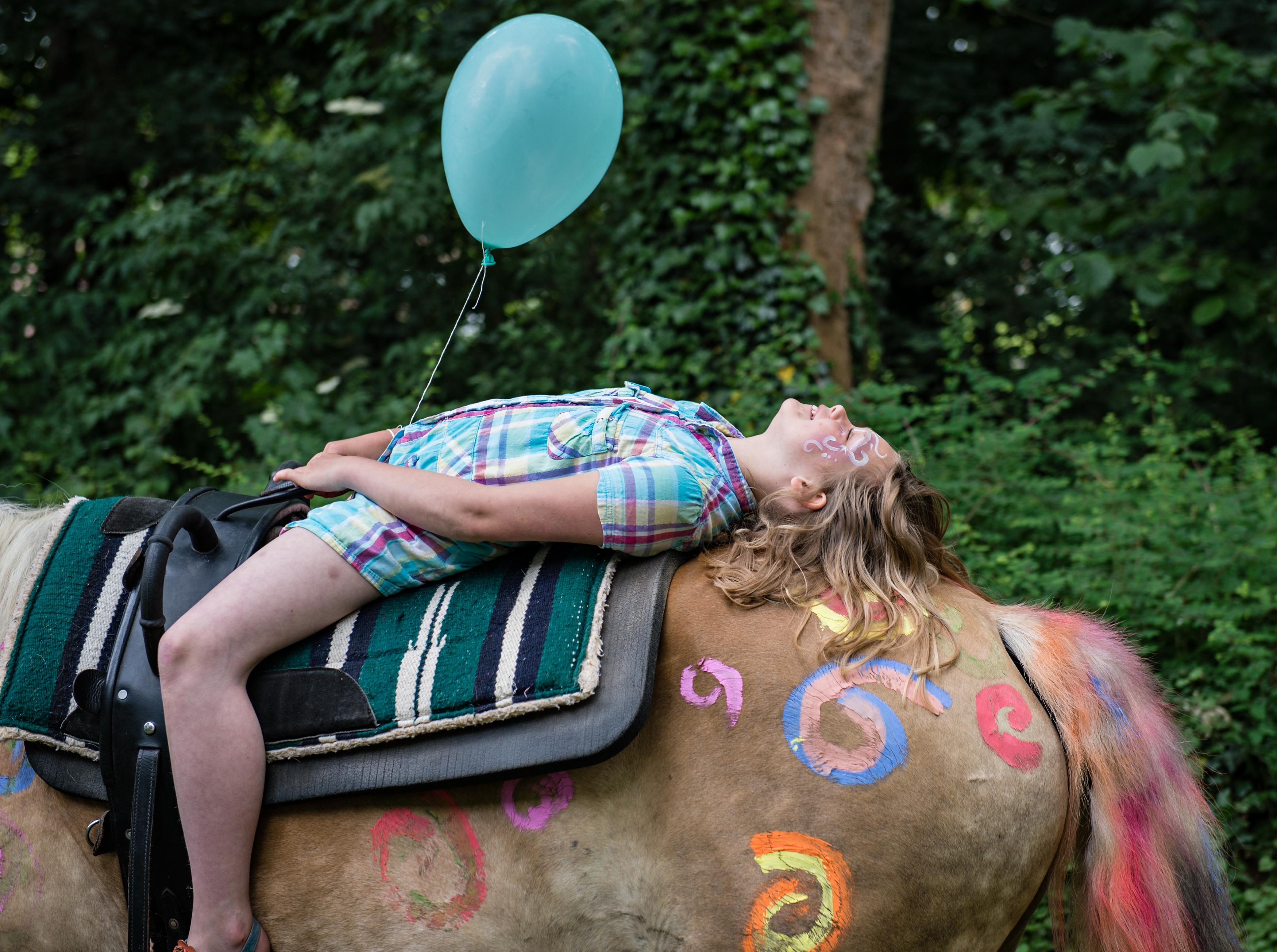 Ein Kind liegt auf einem Pferd und hat einen Luftballon in der Hand