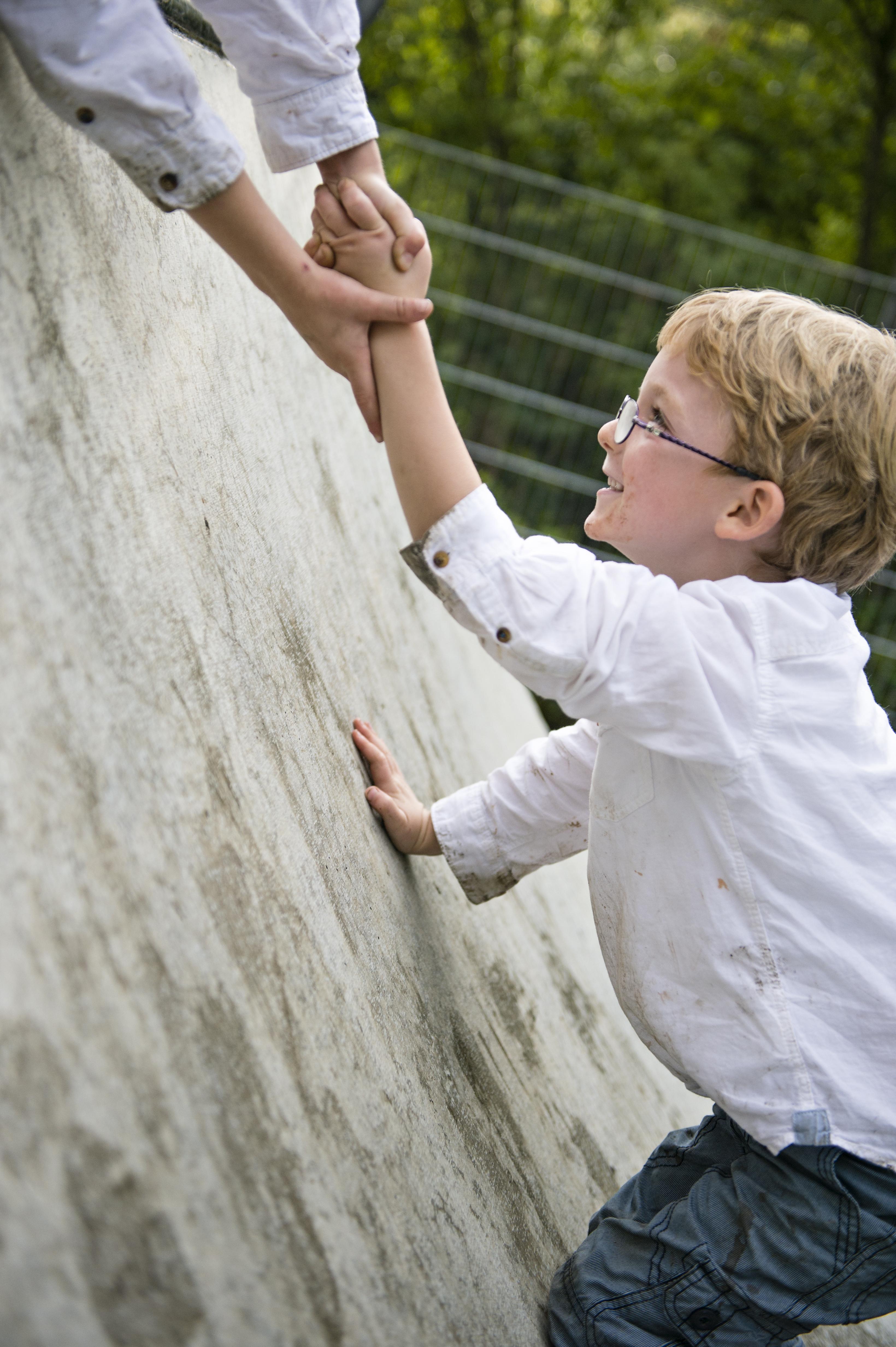 Kind mit Brille hält anderes Kind fest