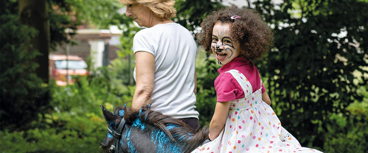 Eine Erzieherin führt ein Pferd, auf dem ein geschminktes Kind sitzt.