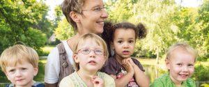 Schwester Jordana wird mit vier Kindern vor dem See gezeigt.