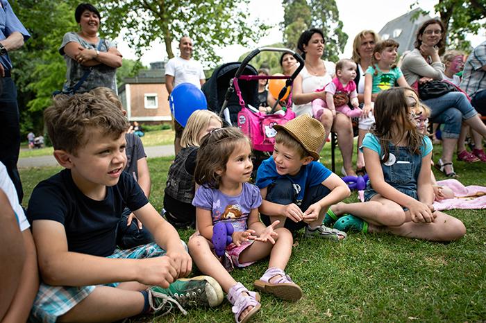 Kinder aus einer Kinderdorffamilie sitzen auf der Wiese