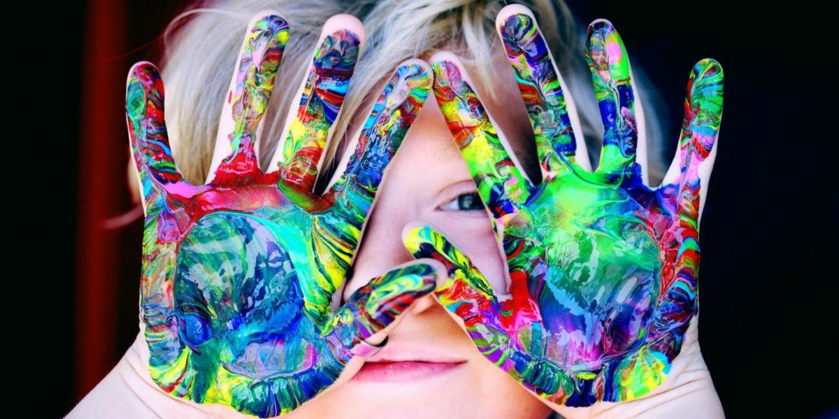 Ein Kind hat sich die Hände bei der Erlebnispädagogik bunt angemalt