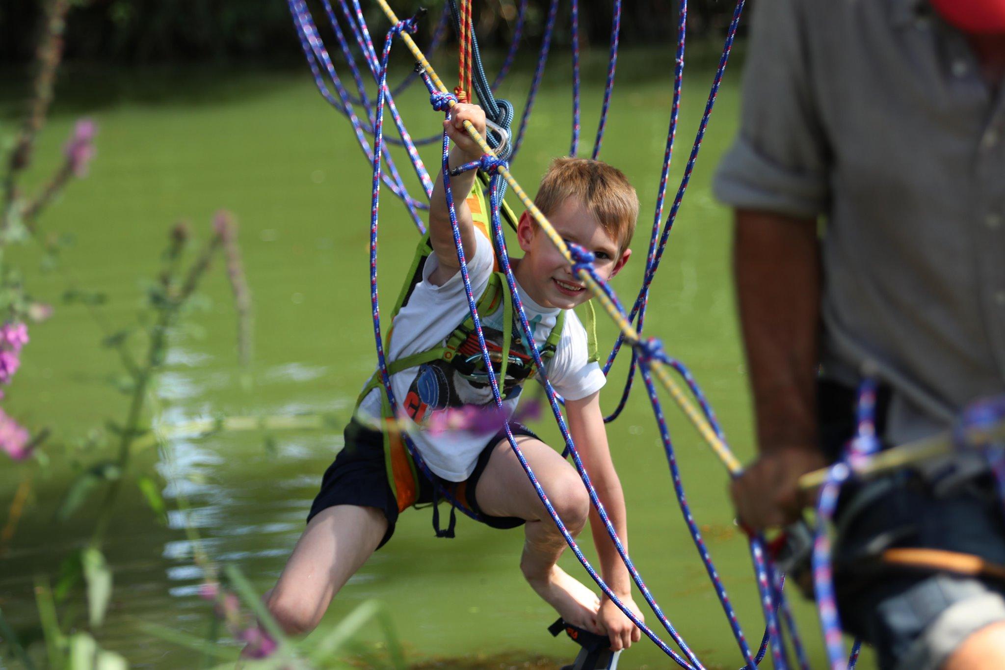 Ein Kind turnt bei einem erlebnispädagogischen Angebot in den Seilen